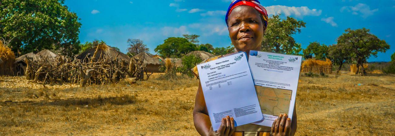 Zambian woman holds land titles.