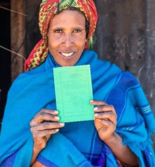 Ethiopian woman displaying land certificate