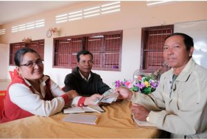 Norng Theourn, FWUC leader (right) meets with members to collect farmer contribution fees and prepare a monthly work plan.
