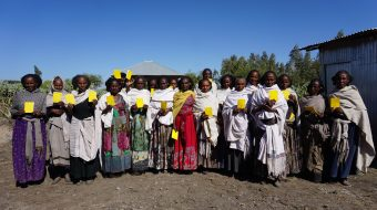 group of Ethiopian women standing holding land title documents
